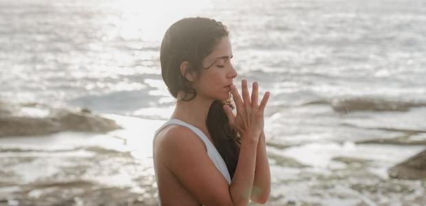 Vrouw die mediteert aan zee